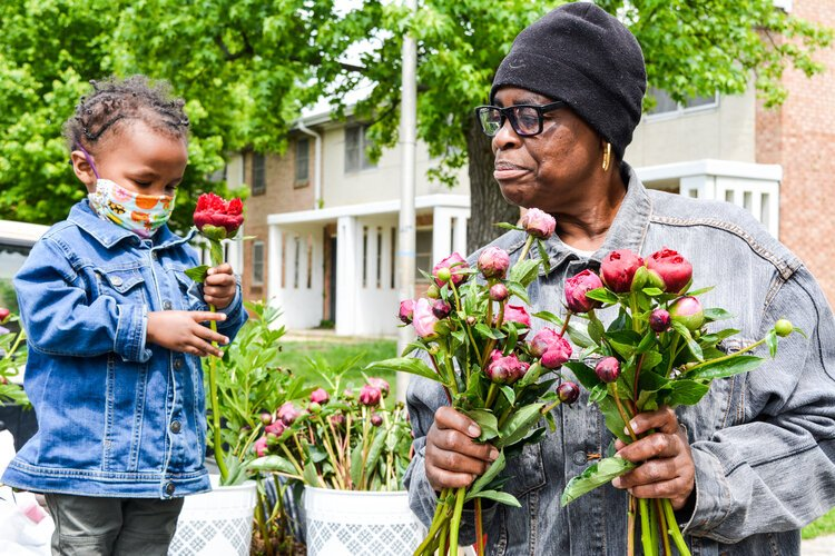 Rosa Key, a community advocate with the Food Justice Network, hands out flowers with her grandson.