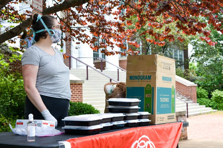A Cville Community Cares team member distributes meals at Venable Elementary.